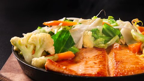 Slide shot delicious Teppanyaki Salmon food with chopsticks and vegetable in the iron pan with smoke.
