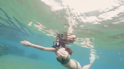Young woman in swimsuit swimming underwater in snorkeling mask and tube. Girl snorkeling and watching coral reef and tropical fish in ocean. Underwater world and marine life.
