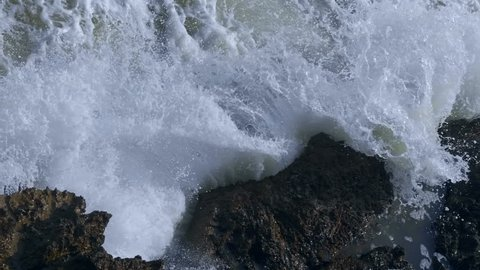The waves of the storm sea hit the rocks and fly around with a lot of splashes