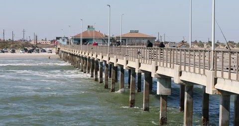CORPUS CHRISTI, TEXAS - 27 JAN 2019: Fishing pier view back to shore and sandy beach Texas. Bob Hall pier on Padre Island near Mustang Island, Corpus Christi Texas. Gulf of Mexico shore. Sandy beach.