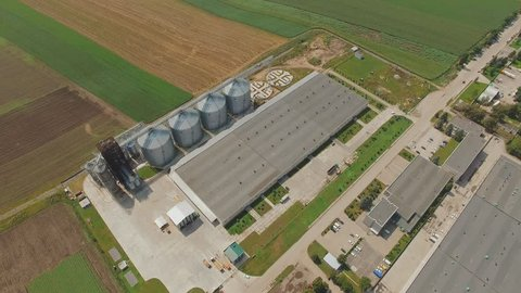 Top aerial view of agriculture grain silos storage tanks. Non-urban. Factory 4K