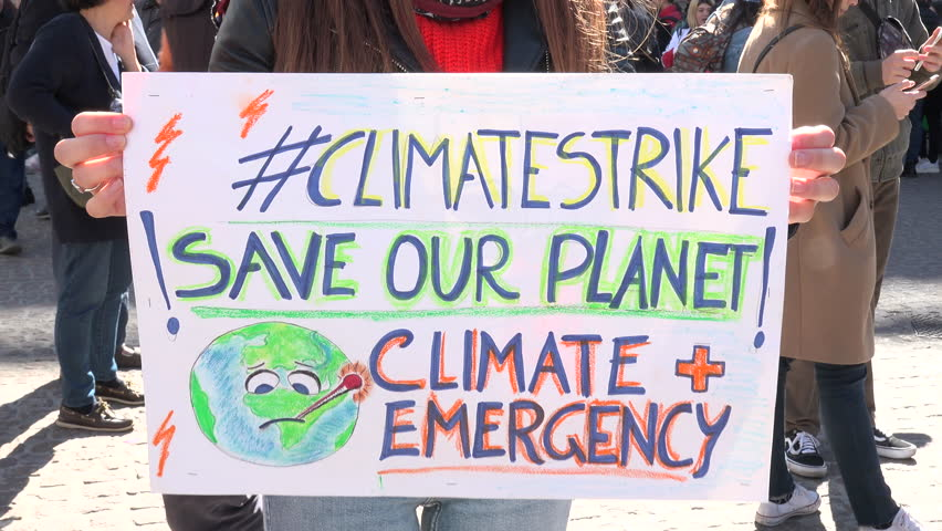 """MILAN, ITALY - MARCH 15, 2019:  Colorful picket sign for global strike for climate. Friday for future, Greta Thunberg ecological movement, placard of activism """"SAVE OUR PLANET CLIMATE EMERGENCY"""""""