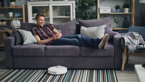 Happy student is using smartphone looking at screen and smiling relaxing on comfortable couch while robotic vacuum cleaner is vacuuming carpet and floor.