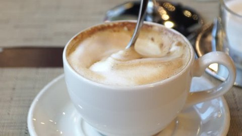 Close-up of cappuccino coffee cup stirred with spoon