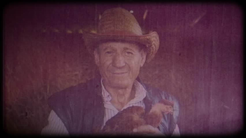 A farmer in a straw hat is holding a brown chicken. Video archive. Retro. Vintage. Farm animals. Raising animals for meat. Agriculture. Organic food. Ranch. Not vegetarianism, but meat-eating | Shutterstock HD Video #1025821769