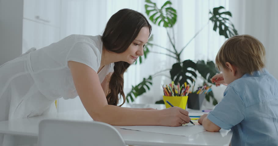 Mom helps son to perform preschool homework to draw a pencil drawing sitting at the table in the house | Shutterstock HD Video #1025823989