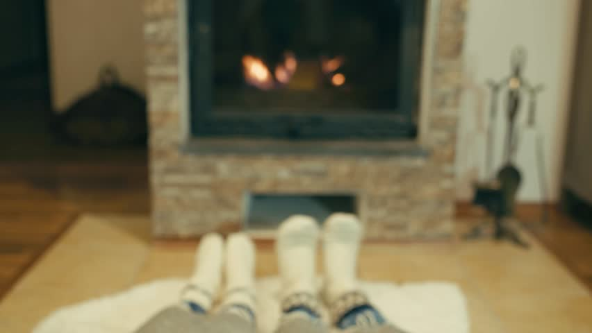 Couple resting by fireplace, Cheerful mother and child at home in knitted socks, near the fire, winter, christmas time | Shutterstock HD Video #1025842079