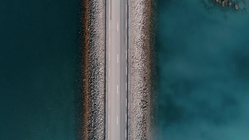 Straight down aerial shot on bridge or rised up road connecting two sides of lake or bay through beautiful blue water. Concept logistics and transportation. Camper van or caravan on travel roadtrip
