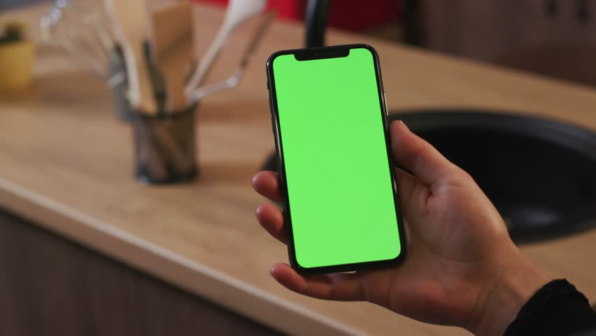 Tokio, Japan - April 7, 2018: Close up woman hand hold use smartphone with vertical green screen on kitchen at home breakfast business food girl house shopping healthy internet abstract slow motion | Shutterstock HD Video #1025899409