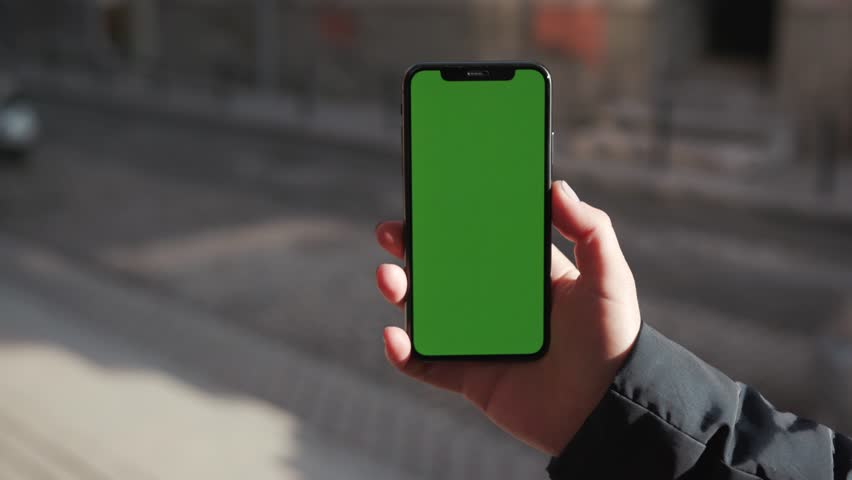 Lviv, Ukraine - May 19, 2018: Hands holding use touch phone with horizontal green screen on city street background sunset people car busy finger touch message cellphone display girl slow motion | Shutterstock HD Video #1025899469