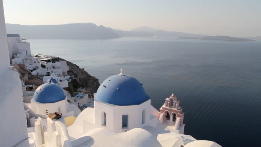 Picturesque view of blue church domes in Oia Santorini overlooking the majestic seascape of Santorini | Shutterstock HD Video #1025920559