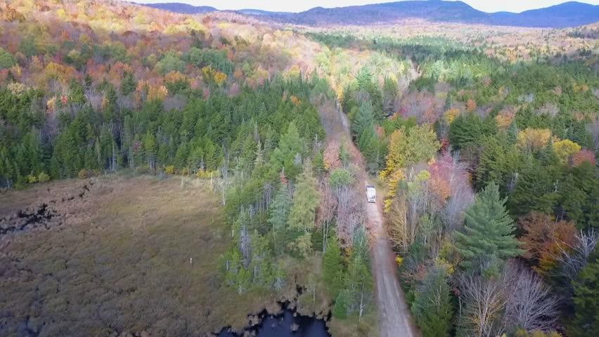 Camper truck drives through colorful autumn forest near wetlands | Shutterstock HD Video #1025940209