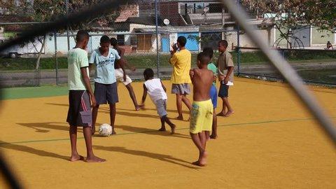 Rio de Janeiro/Brazil - 26th September 2013: young local Brazilian boys playing football in park barefoot filmed through gate mesh