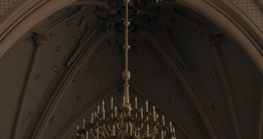 Panoramic view of gothic church interior with two people inside. Cathedral with organ music. High cells with historical light. Jesus Christ portrait on the wall. Vintage gothic style Chandelier.  Warm | Shutterstock HD Video #1025948249