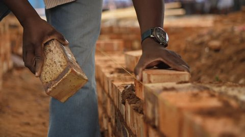 Black construction worker places bricks in wall with cement