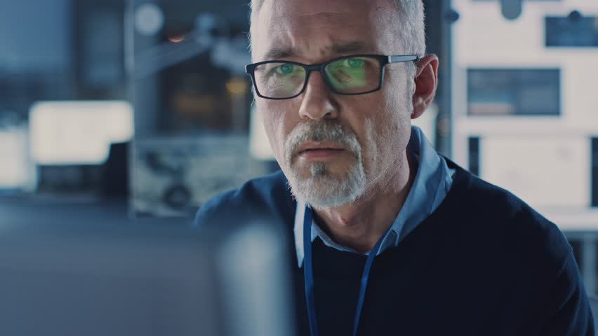 Portrait of Handsome Middle Aged Engineer Wearing Glasses Works on Personal Computer. In the Background High Tech Engineering Facility. Shot on 8K RED Camera. | Shutterstock HD Video #1025971229