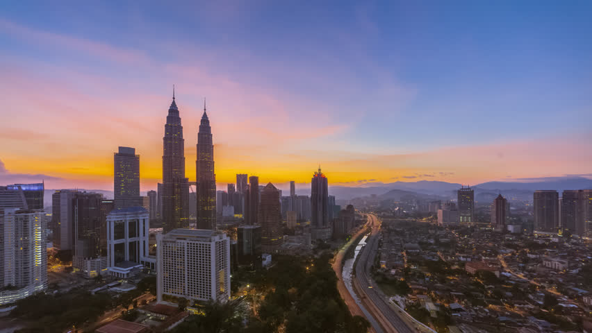 Aerial time lapse view of a city skyline with busy streets and expressway of  Malaysia at sunrise from twilight to day.  | Shutterstock HD Video #1025974949
