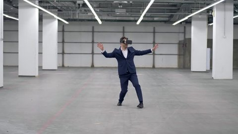 One man playing in office room, wearing VR glasses.