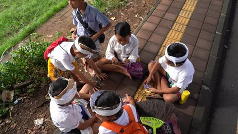 UBUD, BALI, INDONESIA - MARCH 20, 2019 : Unidentified Indonesian school children after class playing cards on the street in village Ubud, island Bali, Indonesia