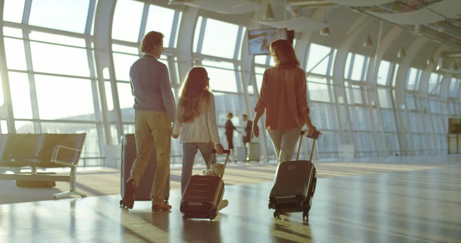 Back view on the Caucasian family - mother, father, daughter - walking the airport hall and carrying their suitcases on the wheels before the departure to the vacation. Rear. | Shutterstock HD Video #1026000569