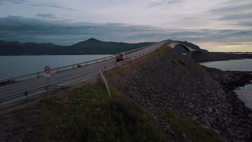 Drone flying above the world famous Atlantic Ocean Road at sunset on an overcast day following a red car vehicle driving over the large bridge between scattered islands