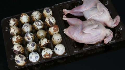 Fresh meat of quail in a plastic brown tray next to the quail eggs on a black background
