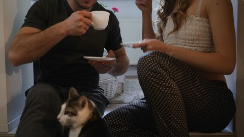 Young family couple sit on the floor drinking hot tea in the morning with cat pet walking nearby