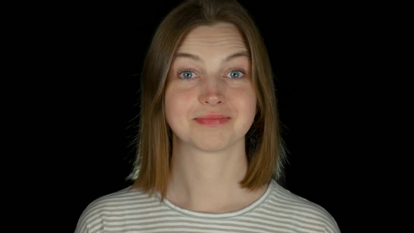 Young long-haired caucasian girl makes grimaces in black studio for casting | Shutterstock HD Video #1026059369