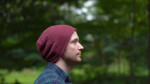 Tracking Side View Portrait of Happy Young Man With Beanie Walking in Park