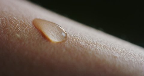 Slow motion macro of fresh cleansing water drop falling on an young smooth healthy human skin. Shot in 8K