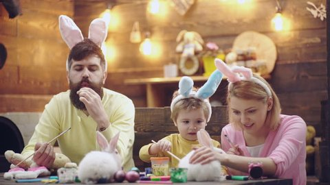 Happy family are preparing for Easter. Cute little child boy wearing bunny ears. Happy spring days. Easter eggs on wooden background. Funny Easter Animals. Preparing for Easter celebration