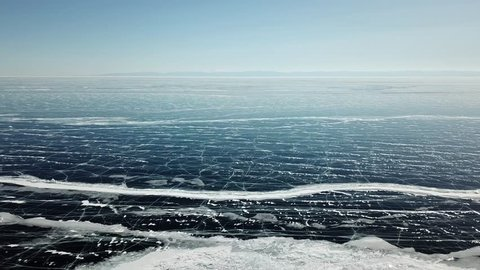 Aerial panoramic view of the Baikal lake at winter season. Spiderweb cracks on frozen ice surface and far mountain on horizon under clear blue sky. Perspective view from high.