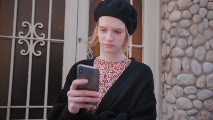 Close up of attractive young Caucasian woman in beret and stylish vintage outfit near her house using smartphone to check social networks, mail, Instagram, staying connected with family and friends