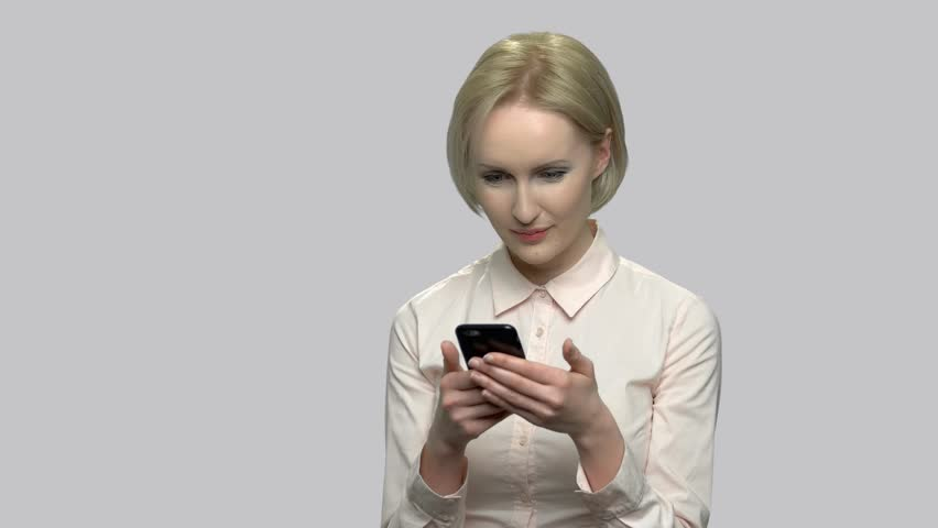 Attractive business woman using cell phone. Happy smiling business lady with smartphone on gray background. People, technology, online communication. | Shutterstock HD Video #1026210899