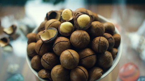 A handful of macadamia in a plate close-up. Hand rotates around its axis plate. Natural light, indoors, real time.
