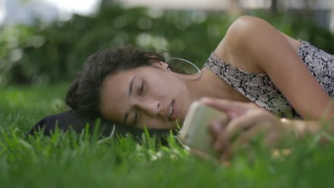 Young Diverse Woman in Park Lying on Side Looking at Phone - Mid Close Up Slow Motion
