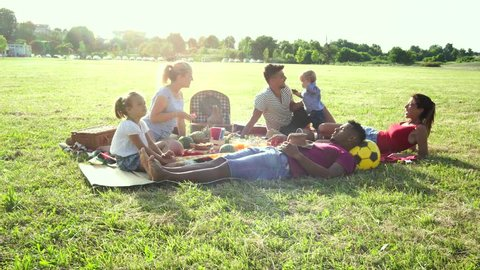 Happy multiracial families having fun together with kids at pic nic party outdoors - Multiethnic joy and love concept with mixed race people playing with children at park - Warm backlight color tones
