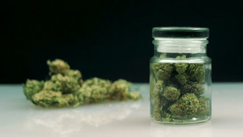 Cannabis catalog product shooting. Cannabis jar reveals, white table, buds on background.