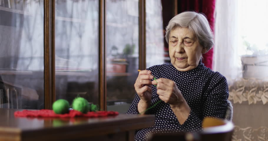 Senior woman sits and knits. Old woman is engaged in knitting. Craft. Hobby. | Shutterstock HD Video #1026290219