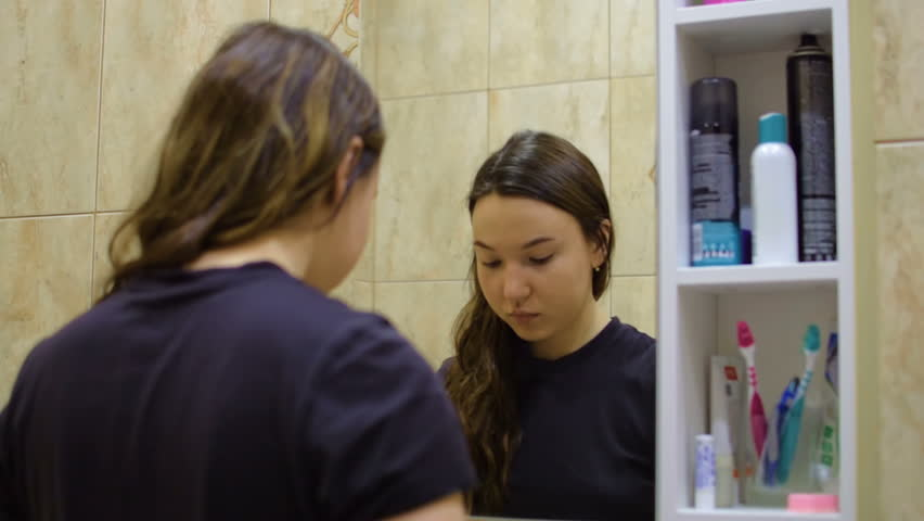 Girl cares for the skin. Looking in the mirror  | Shutterstock HD Video #1026295019