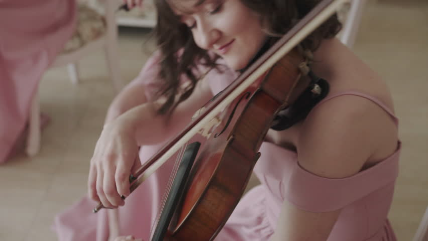 Exultant girl plays on viola with enthusiasm in light room at camera. 4K   Shutterstock HD Video #1026295589