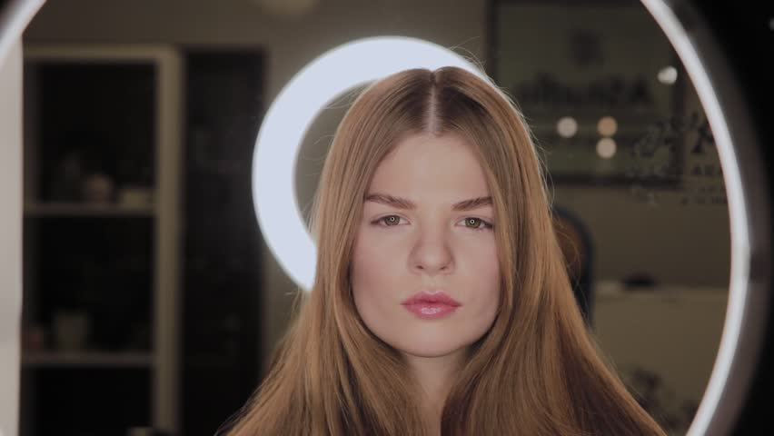Portrait of a girl with a reflection of the annular LED light in the eyes. | Shutterstock HD Video #1026328319