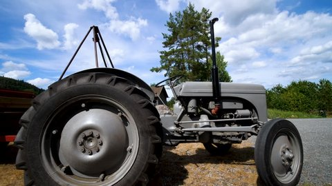 Static, slow motion, tilt shot, of a grey, old fashion tractor, at a farm, on Norwegian countryside, on a sunny, summer day, in South Norway