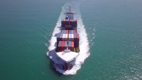 Aerial footage of a large container ship roaring across the open sea.