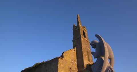 Angel statue kneeling in prayer before ancient irish church building ruin  golden summer sunshine