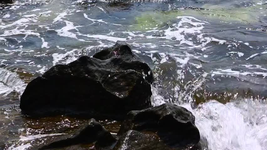 Sea waves crashing with splash on rocky shore. Big Rocks washed by the waves #1026587459