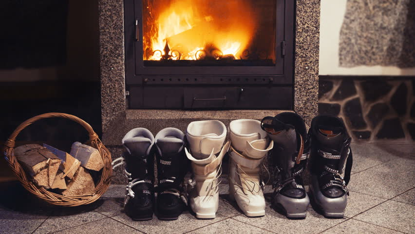 4k three pairs of skiing boots sit near glowing fireplace and basket of kindling. Winter holidays concept. | Shutterstock HD Video #1026612779