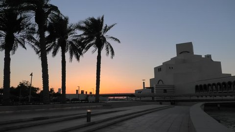Scenic seafront landscape of Doha Bay Park with palm trees and dhow at sunset sky. Urban cityscape of Doha, Qatari capital. Middle East, Arabian Peninsula in Persian Gulf.