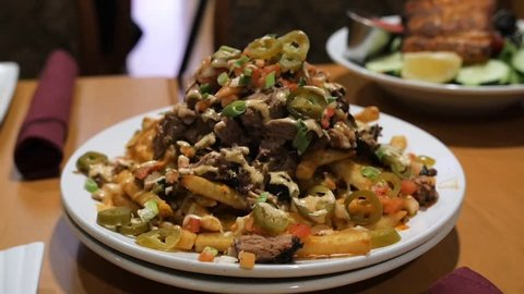 hillbilly french fries toped with cheese beef brisket fry sauce jalepenos. Clockwise circular panning shot of hillbilly french fries topped with cheese, beef brisket, fry sauce, and jalapeños.