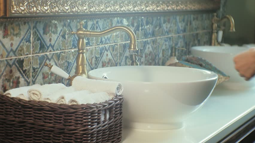 A woman washes her hands in a beautiful toilet, takes a white towel from the basket and dries them, hands close-up, cleanliness concept